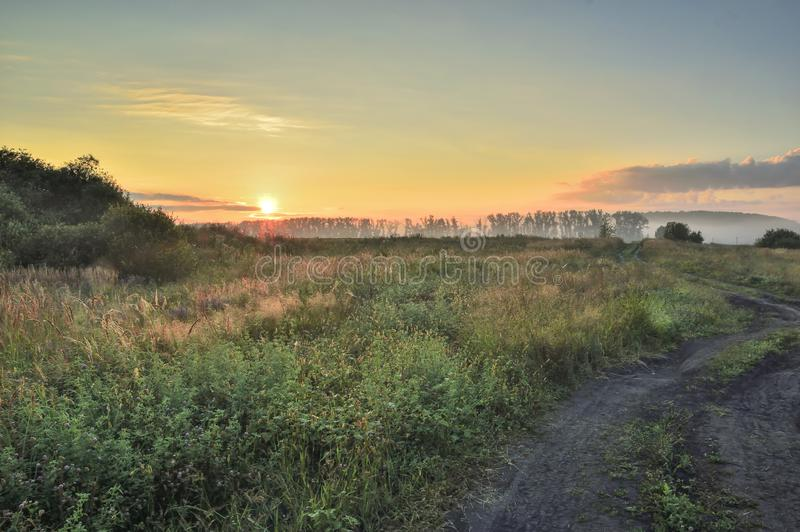 Morning, rising sun over the field and dirt road, with trees and country buildings stock image