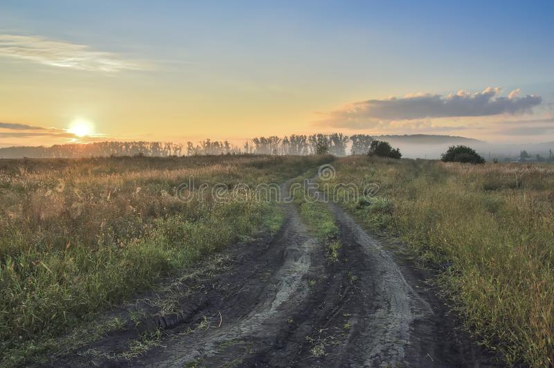 Morning, rising sun over the field and dirt road, with trees and country buildings stock photo