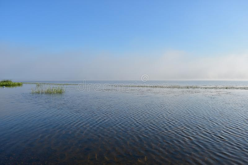 Morning river fog creeps over the water beautiful view blue sky clouds reflected in the water. Reservoir stock photos