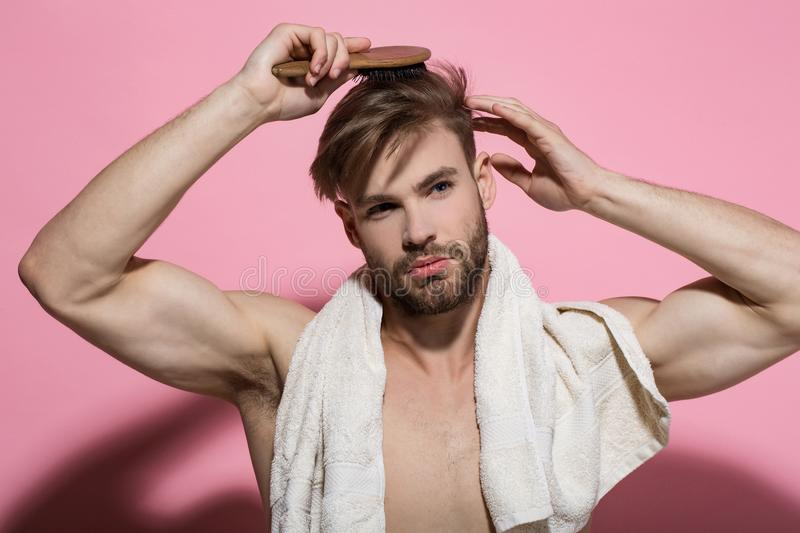 Morning routine concept. Macho with bath towel on sexy chest. Beauty, grooming, hygiene. Haircare, wellness, health. Man brush hair with hairbrush on pink stock image