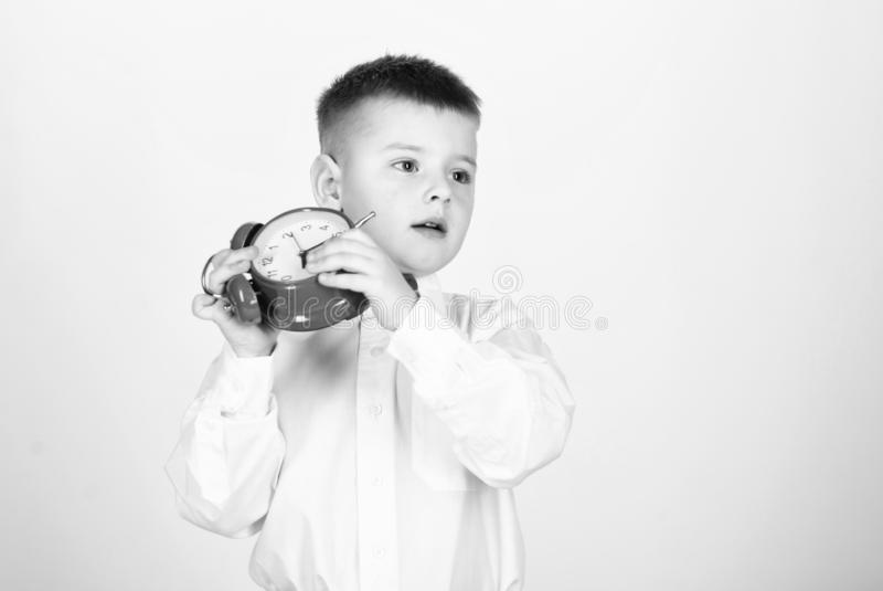 Morning routine. Schoolboy with alarm clock. Kid adorable boy white shirt red bow tie. Develop self discipline. Set up. Alarm clock. Child little boy hold red royalty free stock photo