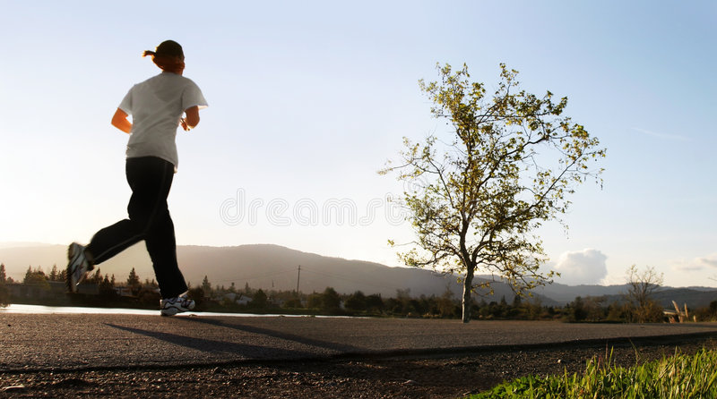 Morning run. Woman jogging along a river in the morning stock image
