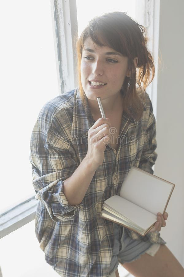 Morning scene of young hipster woman right hand writing on noteb royalty free stock photography