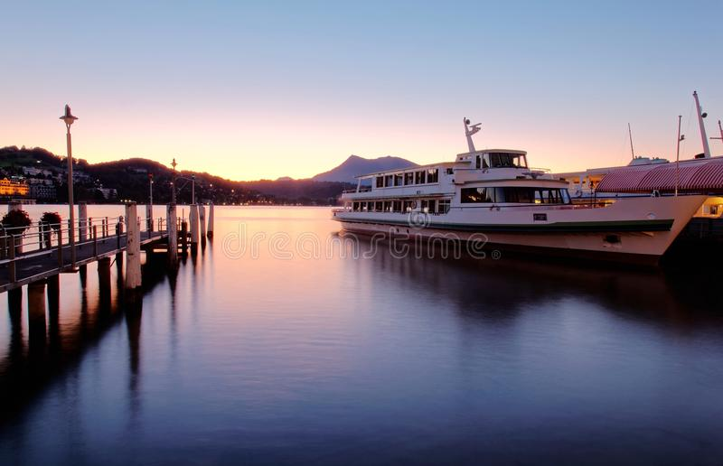 Morning scenery of Lake Lucerne at sunrise with view of a cruise ship parking by a wooden dock. Silhouettes of distant mountains & the golden light of dawning royalty free stock photography