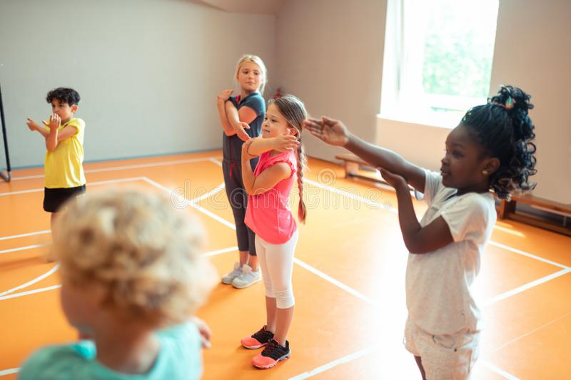Elementary school children working out at sports lesson. Morning at school. Happy elementary school children working out in the gym during their sports lesson royalty free stock photography