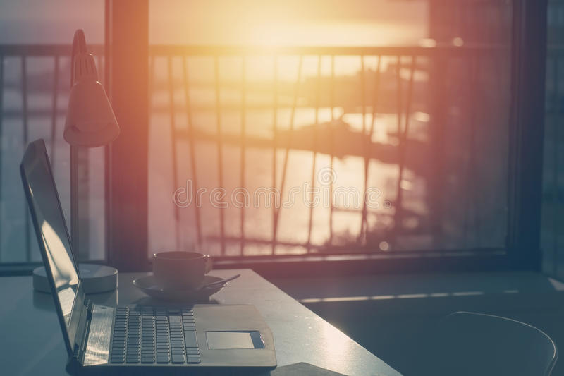 Morning with a sea background and warm light. Laptop on the desktop. The concept of freelancing in the style of WORK royalty free stock photos