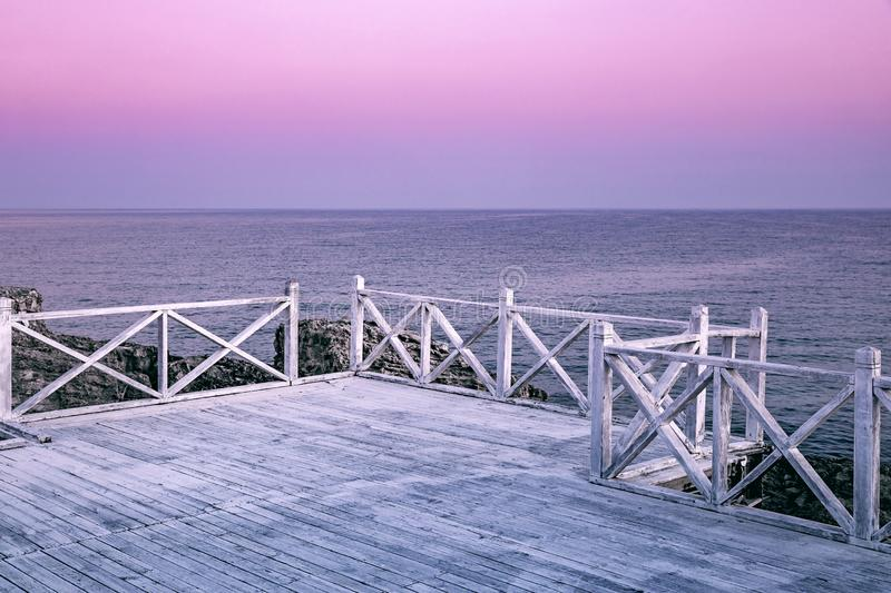 Morning seascape. Calm sea, wooden bridge on a background of pink dawn sky.  royalty free stock photos