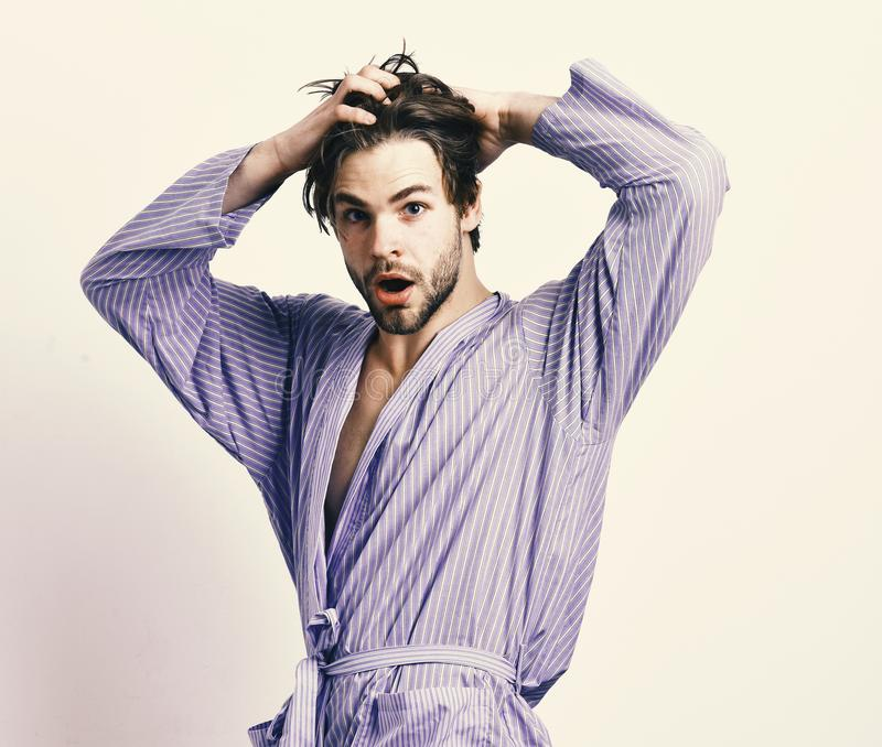 Morning and showering concept. Man with beard in blue dressing gown on grey background. Bearded macho in blue bathrobe. Or leisure wear. Guy touches hair in royalty free stock images