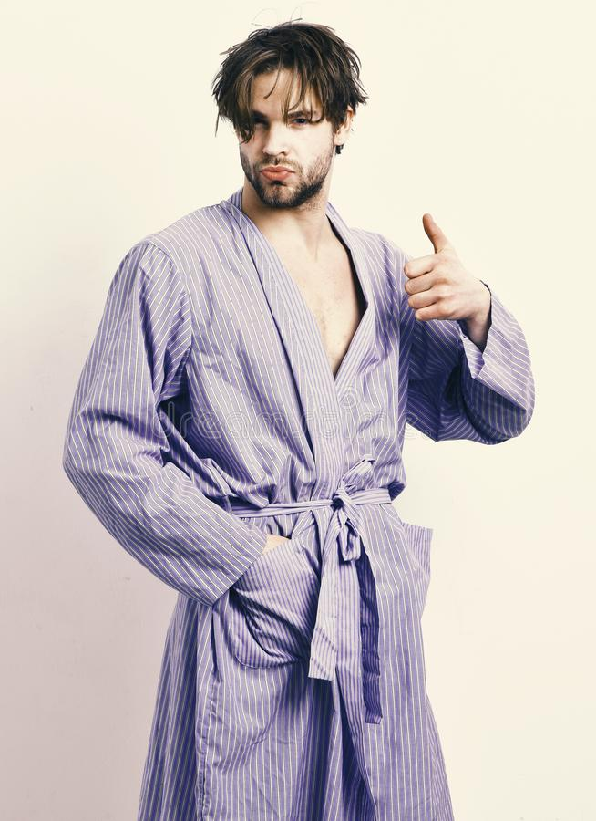 Morning and showering concept. macho in bathrobe or leisure wear showing thumb up. Guy stands in stylish home or bath clothes. Man with beard in blue dressing stock photo