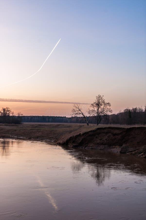 Morning sky met vliegbaan boven de rivier royalty-vrije stock afbeeldingen