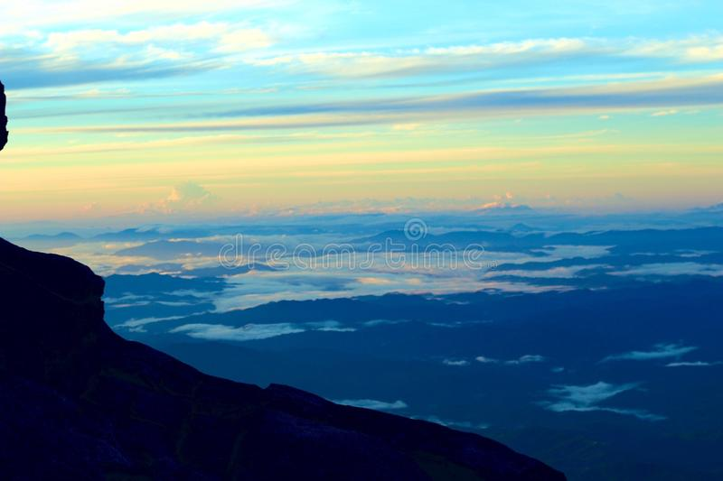 Morning Sky - Mount Kinabalu. Mount Kinabalu July 2019.  Epic view from the mountain. Blues and yellows from the mountainside at 4000m above sea level.  Wisps of royalty free stock photo