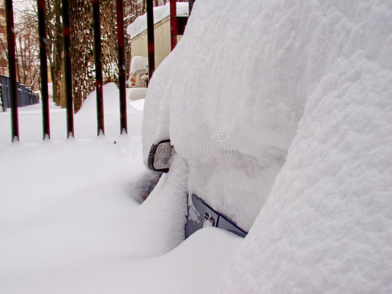 In the morning after a snowfall. Dig up the car. The car is covered with snow. Winter in Siberia. In the morning after a snowfall. Dig up the car. The car is stock photography