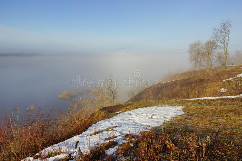 Morning spring fog over the river rises the sun is melting snow. Beautiful scenery stock photography