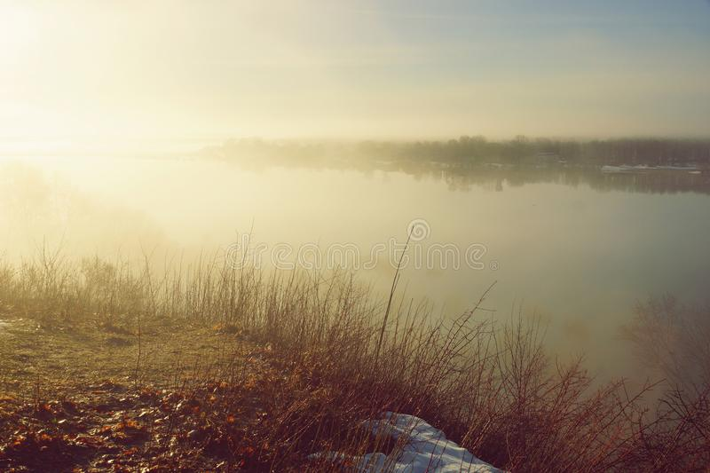 Morning spring fog over the river rises the sun is melting snow. Beautiful scenery royalty free stock images