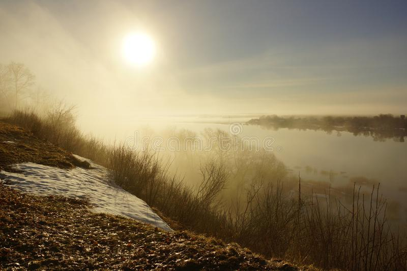 Morning spring fog over the river rises the sun is melting snow. Beautiful scenery stock images