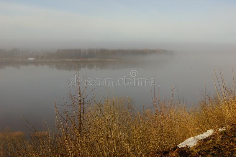 Morning spring fog over the river rises the sun is melting snow. Beautiful scenery royalty free stock image