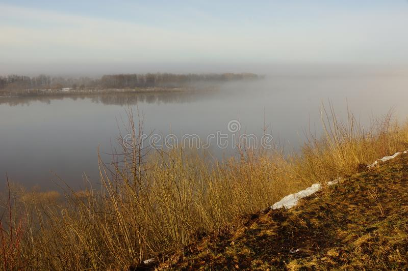 Morning spring fog over the river rises the sun is melting snow. Beautiful scenery stock photo