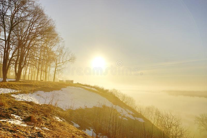 Morning spring fog over the river rises the sun is melting snow. Beautiful scenery royalty free stock photography