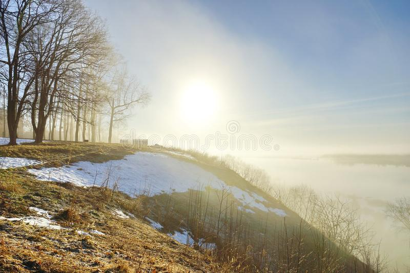 Morning spring fog over the river rises the sun is melting snow. Beautiful scenery stock photos