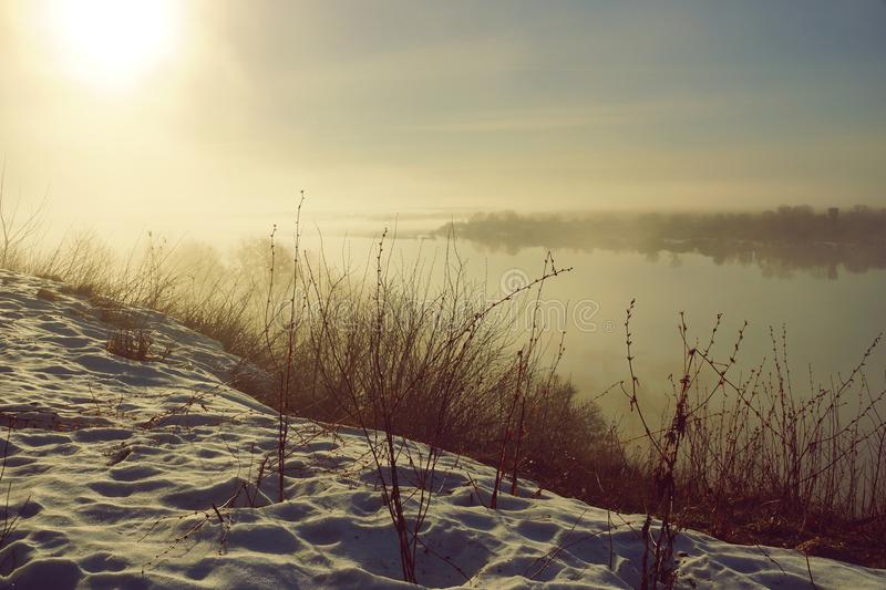 Morning spring fog over the river rises the sun is melting snow. Beautiful scenery stock image