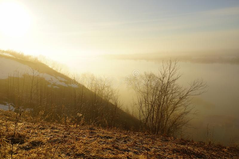 Morning spring fog over the river rises the sun is melting snow. Beautiful scenery royalty free stock photo