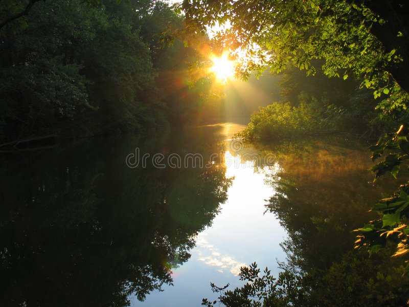 Morning Sun. Sun rising over river giving trees reflection stock photo