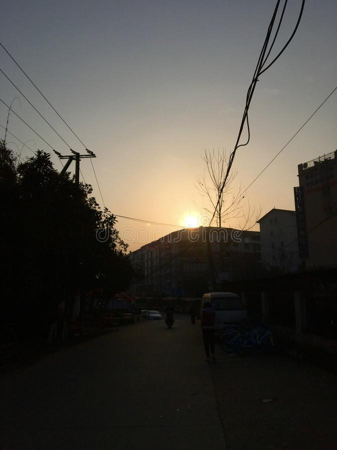 The morning sun just rises above the roof. On a clear Monday, the sky was clean and blue. I happened to meet the rising sun on the road to work, so I quickly royalty free stock photography