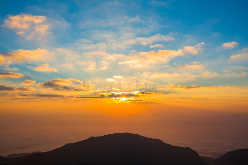 Morning Sun light shine with silhouette mountain and blue cloud stock photo