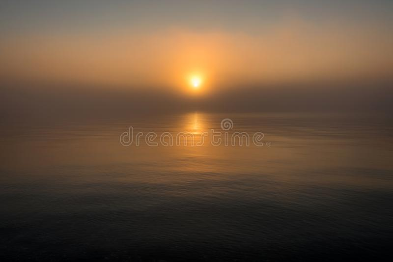 Morning sun over lake, sunrise and reflection in mist. royalty free stock image