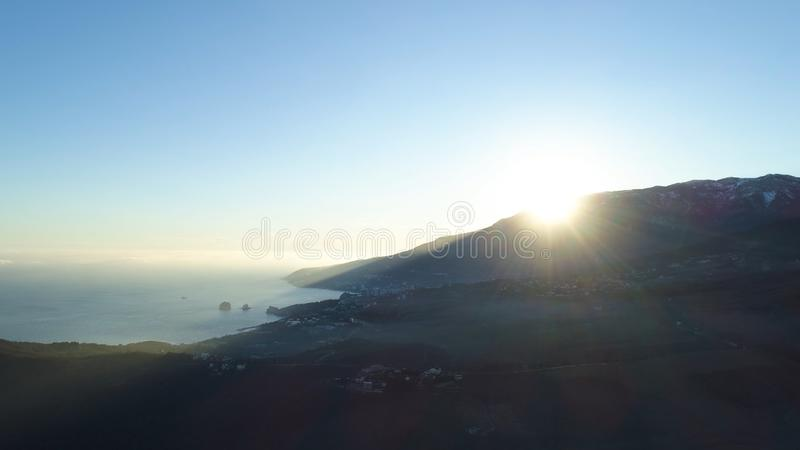 Morning sun rising over a mountain near the sea on blue sky background, beauty of nature. Shot. Picturesque sunrise at stock photos