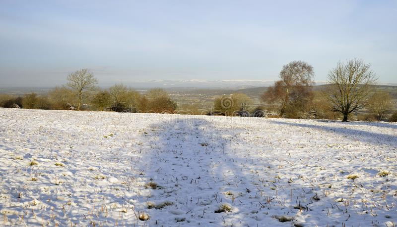 Snow on Burrington Ham. Morning Sun on Snow on Burrington Ham with Hills of South Wales behind, Mendip Hills, Somerset royalty free stock image