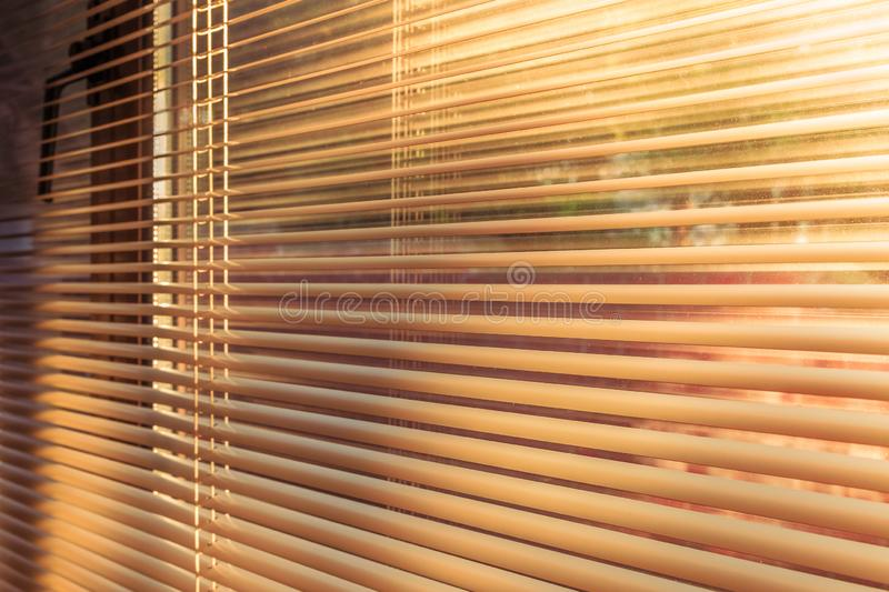 Morning sunlight at sunrise shining through the slats of horizontal venetian blinds. Morning golden sunlight at sunrise shining through the slats of horizontal royalty free stock photo