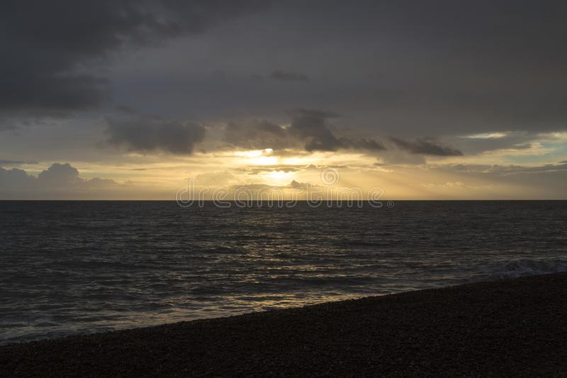 Morning sunrise with sun rays shining through clouds at Aldeburgh stock photo