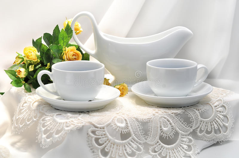 Morning table. The wall in the background is a light off-white. Bowl on table is empty, suggesting the food has yet to arrive.White cups on a white table, a stock photo