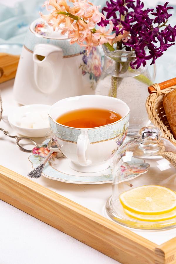 Morning tea concept. Flowers, tea and strudel on a tray stock image