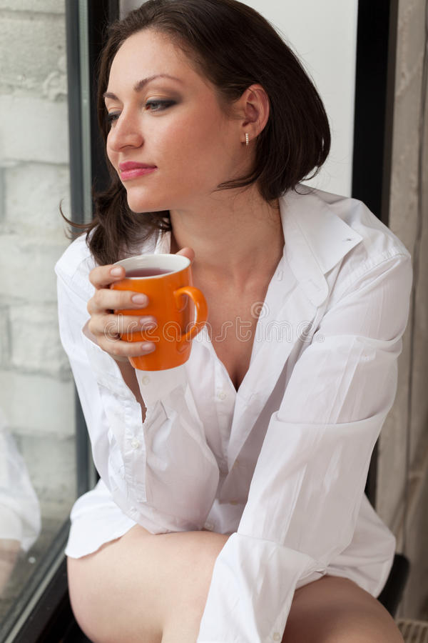 Morning tee. Girl with cup of tee on windowsill royalty free stock photography