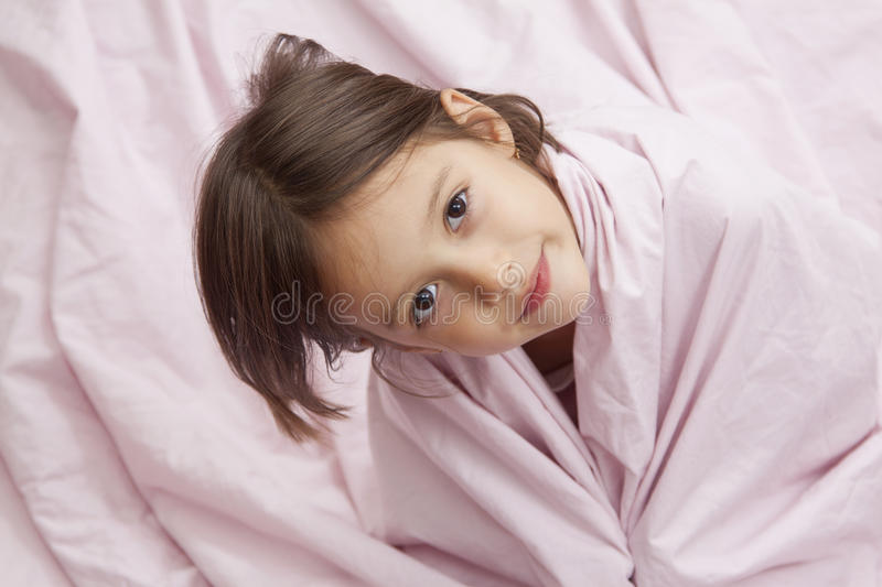 Morning time. Happy girl in bed with pink pillow stock image