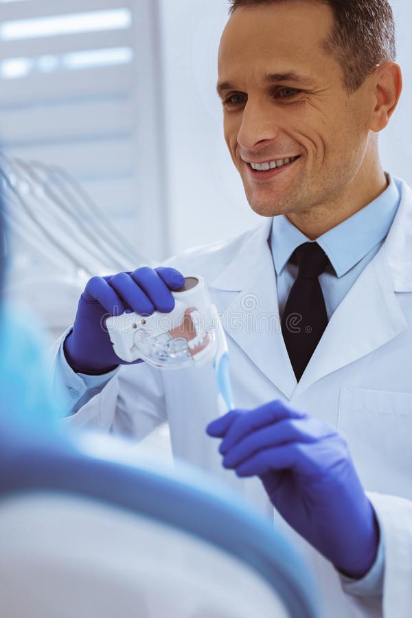 Attractive young man working in stomatology clinic. Morning tradition. Handsome brunette wearing rubber gloves while cleaning plastic teeth stock photos