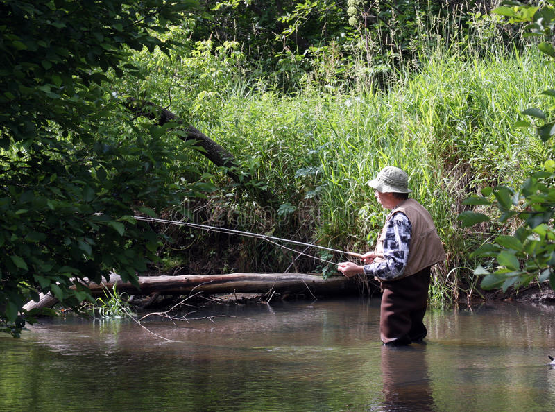 Morning trout fishing. Trout fisherman in early morning sun on a stream stock photos