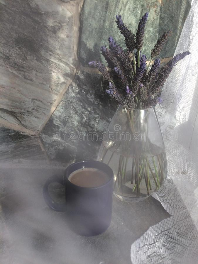 Lavender Glass vase and coffee with rock stone wall next to the window stock photos