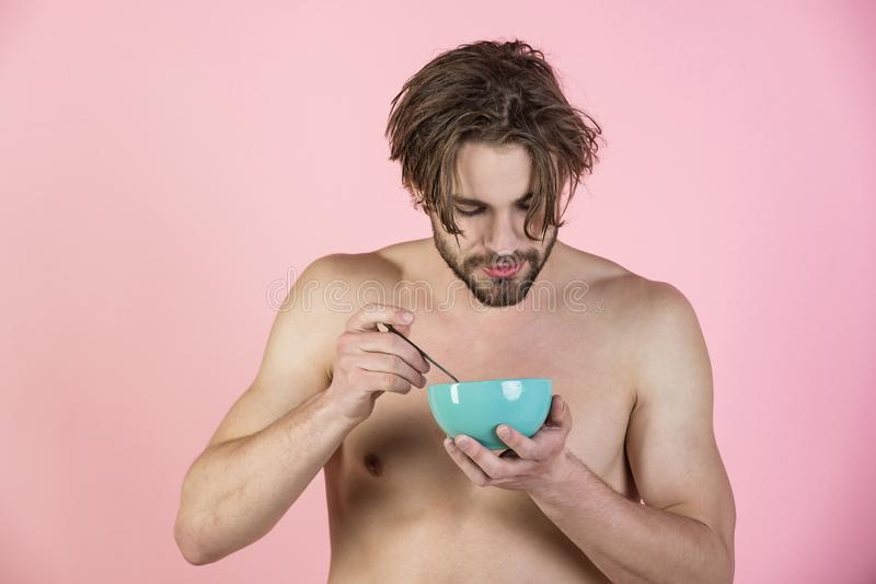 Morning, vegetarian, organic food. Dieting and fitness, calorie. Sexy man with muscular body eating cereal, healthcare. Man with wet hair eat breakfast on pink royalty free stock photo