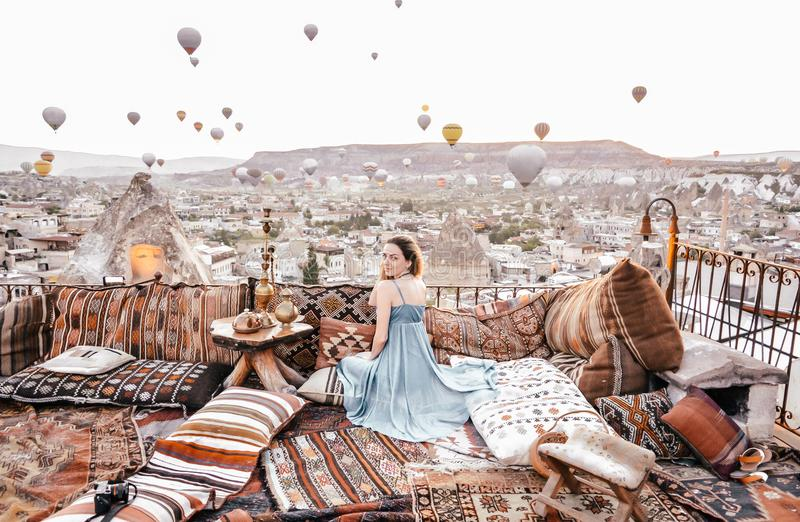 Morning view in Cappadocia. Terrace view in Goreme woman with hot air balloons and carpets stock image