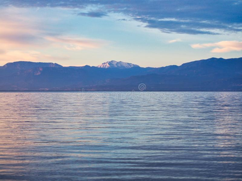 Morning View Over Gulf of Corinth to Snow Capped Peloponnese Mountain. Early morning dawn view over the Corinthian Gulf to fresh snow on a Peloponnese mountain royalty free stock photography