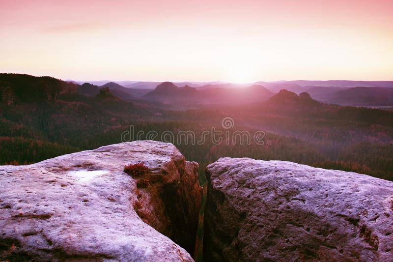 Morning view over sandstone cliff into forest valley, daybreak Sun at horizon. royalty free stock image
