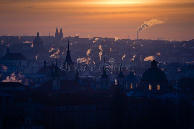 Morning view of winter Prague city full of smoking chimneys royalty free stock photography