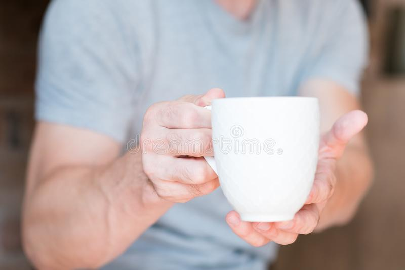 Morning wake coffee time man cup energy. New day. Morning wake up drink. Coffee time. Man offering white cup of energy beverage royalty free stock photos