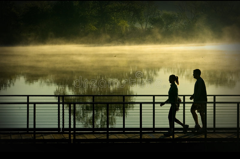 Morning Walk. Silhouette of a man and woman on a morning walk royalty free stock images