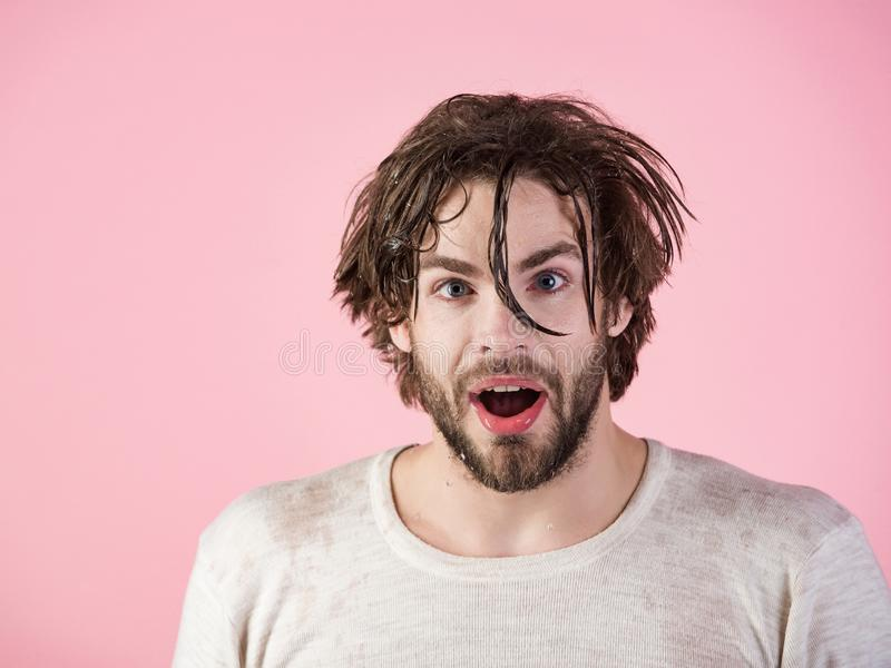 Morning washing, wake up, everyday life. Man splash water at face on pink background. Hygiene, guy wash surprised face. Refreshment and healthcare. Man with stock images