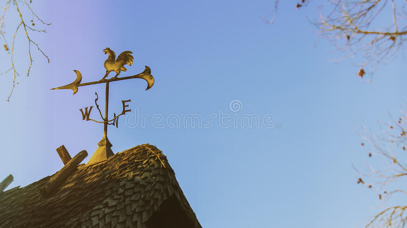 Morning Weather Vane Rural. A decorative weather vane on top of a rural looking house with autumn trees surrounding. Shot early morning right as the sunrise stock photos