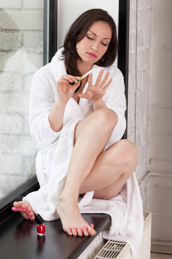 Morning on windowsill. Girl in bathrobe making manicure and pedicure royalty free stock photo